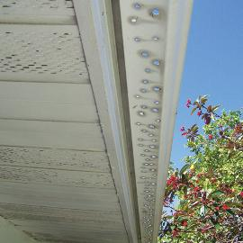 This gutter wouldn't drain properly because it was sloped incorrectly. Instead of lowering the end with the downspout a few inches, they drilled hundreds of holes, thus defeating the purpose of having a gutter at all.